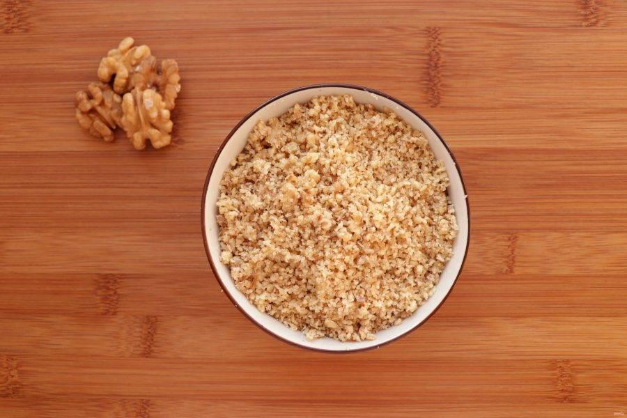 Тем временем приготовьте ореховый соус. Грецкие орехи измельчите в блендере или пропустите через мясорубку.