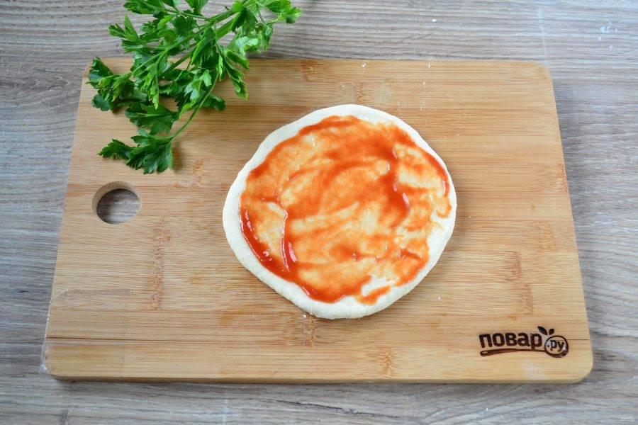 Тесто подошло и можно начинать заниматься формовкой маленьких пицц. Тесто разделите на 5-7 частей, в зависимости от того, сколько пицц вы хотите получить. Раскатайте каждую часть в форме круга толщиной 1 см. Каждый кружок смажьте томатным соусом (можно кетчупом, но у меня томатный соус домашнего приготовления).