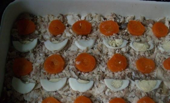 В блюдо, в котором наш холодец будет настаиваться, выкладываем измельченную рыбку, нарезанную кружочками морковь, кружочки вареного яйца, можно добавить зелени - петрушки.