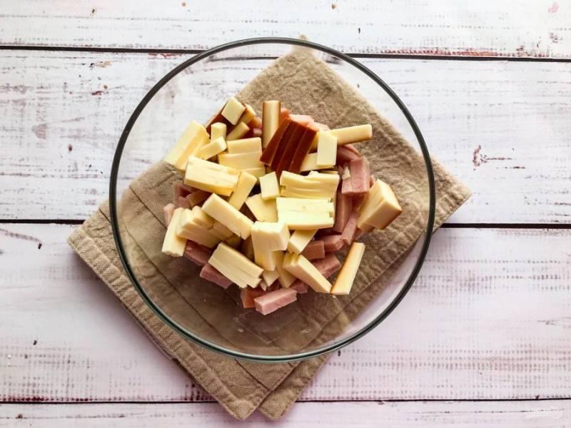 Копченый сыр нарежьте соломкой и добавьте к ветчине.