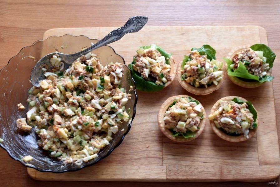 В тарталетки положите по листику салата, выложите порцию салата (удобно это делать ложкой для мороженого) и украсьте сверху красной икрой.
