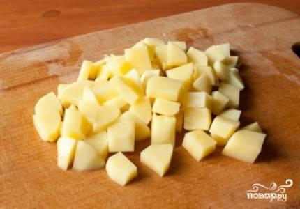 Картофель нарежьте кубиками. Мясо достаньте из кастрюли, процедите бульон и помойте кастрюлю.