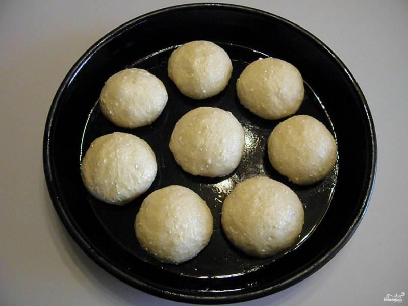 Разделите тесто на равные части. Количество частей по желанию, я разделила на 8 частей, булочки получились очень большие. Сформируйте круглые красивые шарики. Выложите на смазанный рафинированным маслом лист. Оставьте подходить на 20 минут. После смажьте желтком и поставьте в горячую духовку выпекаться. Температура 180 градусов, время 30 минут.