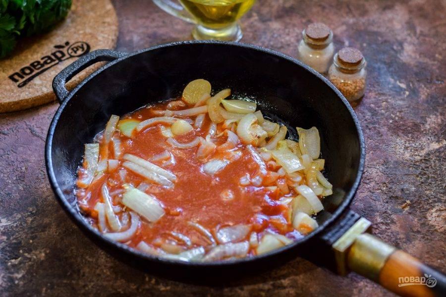 Добавьте к луку томатный соус и перемешайте, всыпьте специи.