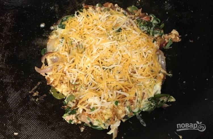 6.Переверните омлет на другую сторону и посыпьте тертым сыром.