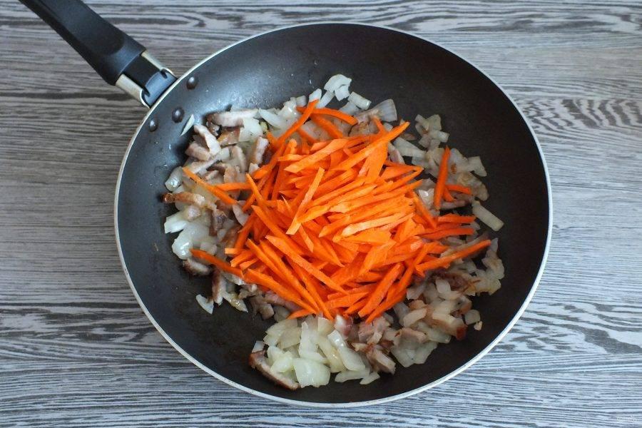 Нарежьте морковь тонкой соломкой и добавьте к обжаренному луку с салом. Перемешайте. Добавьте парус толовых ложек растительного масла. Обжарьте в течение 3 минут помешивая. Добавьте 1 половник бульона и тушите до мягкости моркови.