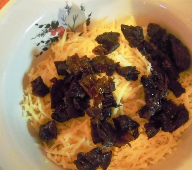 Чернослив режем кусочками и смешиваем с тертым сыром.
