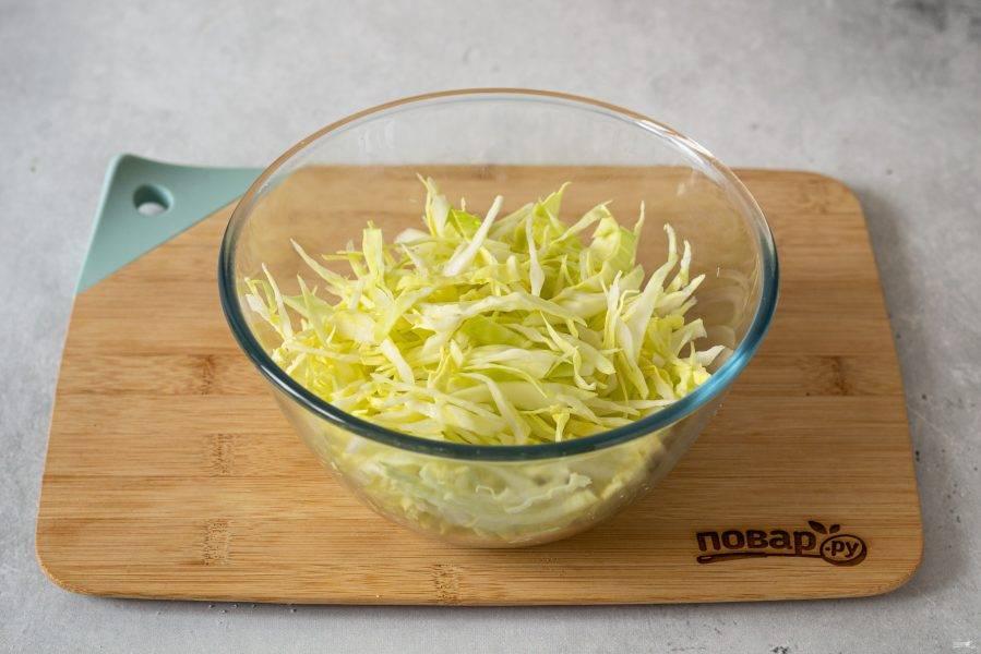 Тонко нашинкуйте молодую капусту.