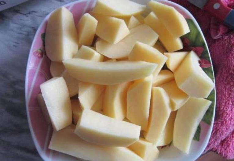 Тем временем почистите и порежьте картофель. Режьте крупными кусками, чтобы во время запекания она не приготовилась раньше ребер.