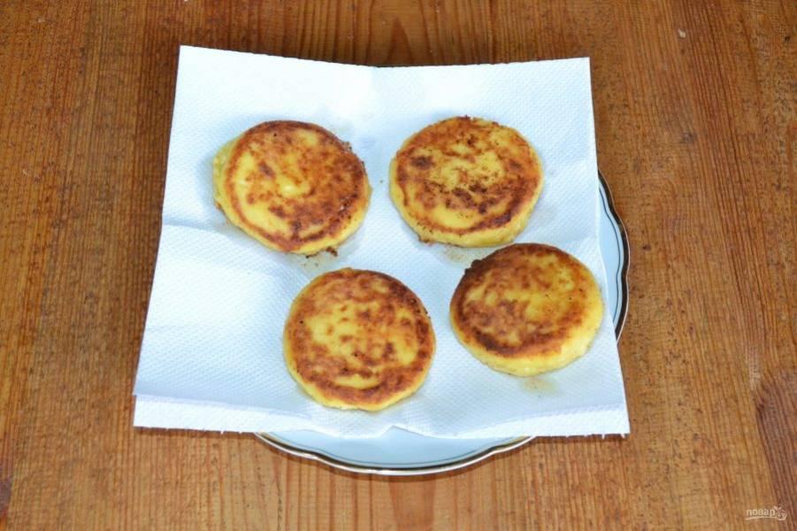 Когда сырники подрумянятся с обеих сторон, выложите их на бумажное полотенце, чтобы убрать излишки масла.