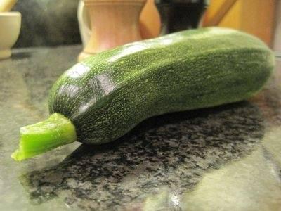 Сначала тщательно промываем под проточной водой кабачок, укладываем на разделочную доску и нарезаем поперек, кружочками толщиной до 1 сантиметра. Измельченный овощ перекладываем в тарелку.