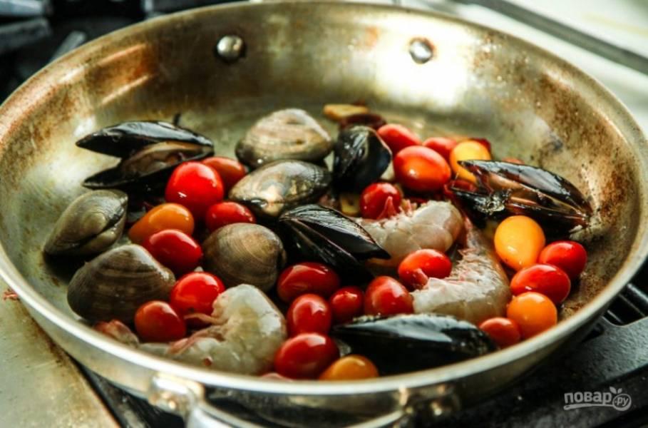 Уберите перец и чеснок, выложите в сковороду промытые морепродукты и помидоры целиком.