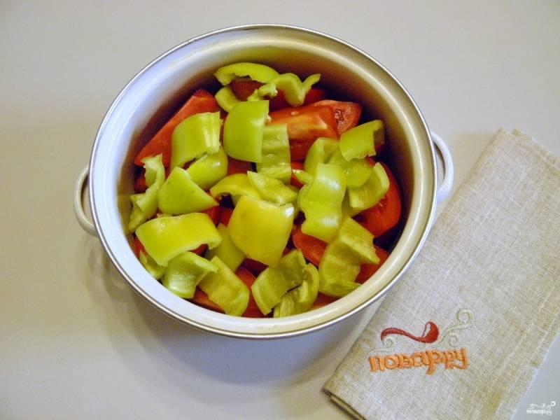 Болгарский перец освободите от семян, помойте внутри и порежьте небольшими квадратами. Добавьте его к помидорам.