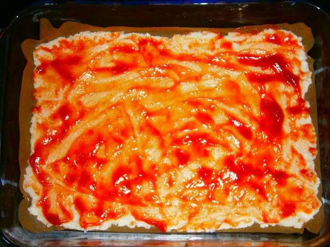 Смажьте тесто тонким слоем кетчупа.