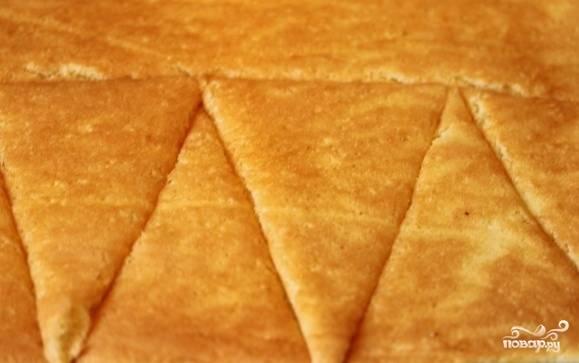 Полученную выпечку перекладывайте на новый пергамент и накрывайте мокрым полотенцем. После того как бисквит остыл, аккуратно снимайте бумагу. Разрежьте его на вытянутые треугольники, чтобы затем выложить в глубокую салатницу в виде «купола».