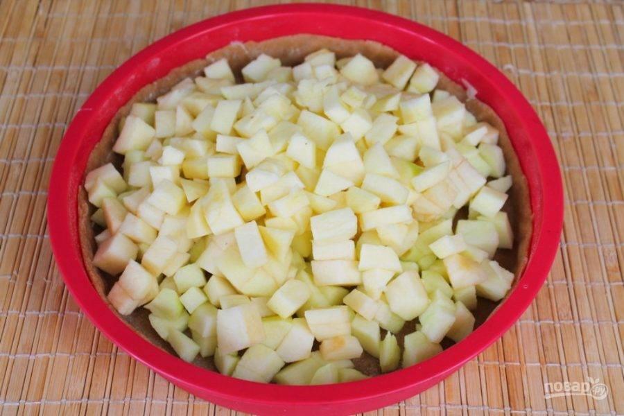 Яблоки чистим, режем кубиками и выкладываем на тесто.
