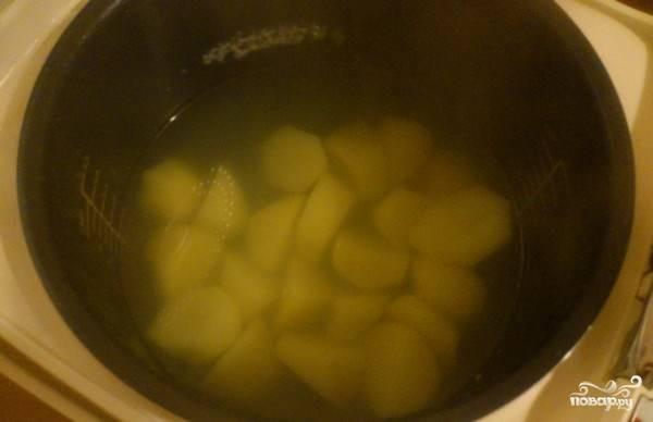 """В чашу мультиварки налейте очищенной питьевой воды. Картофель вымойте, очистите от кожуры и нарежьте на произвольные кусочки среднего размера. Опустите картофель в воду, предварительно ее посолив, выставьте режим """"Варка"""" и отваривайте картофель до полной готовности."""