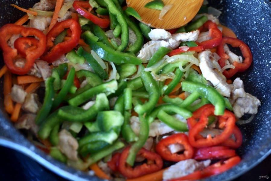 Добавьте к мясу морковь брусочками, сельдерей — тонкими ломтиками и перец, нарезанный соломкой. Помешивая, жарьте минут 5, до полуготовности.