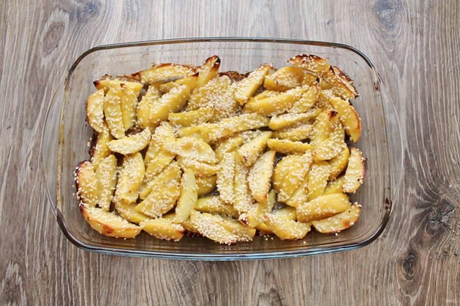 Поставьте в горячую духовку и запекайте картофель в кунжуте при температуре 180 градусов в течение 40-60 минут, до готовности. Разложите по тарелкам и подавайте к столу.