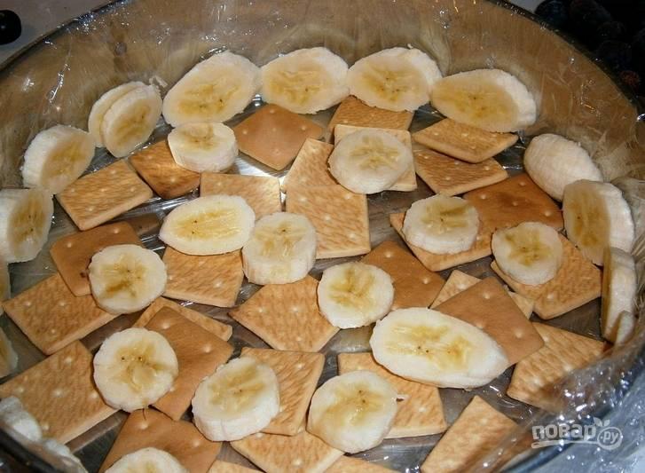 2. Теперь выкладываем на дно формы основу. У меня это слой крекеров пополам с бананом, но это также могут быть любые твердые фрукты.