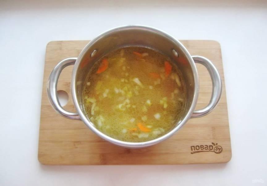 Выложите морковь с луком в кастрюлю и продолжайте варить суп.