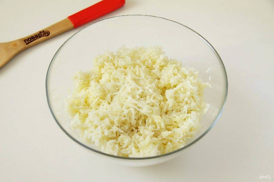 Натрите картофель на крупной терке и переложите в глубокую миску.