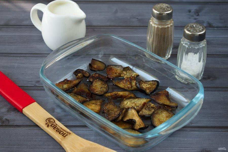 2.Баклажан нарежьте тонкими ломтиками, разложите на противне, брызните маслом, посолите, поперчите по вкусу. Поставьте запекаться в духовку на 15 минут при 200 градусах.