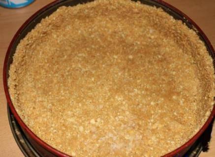 На дно формы кладем печенье и тщательно его утрамбовываем.