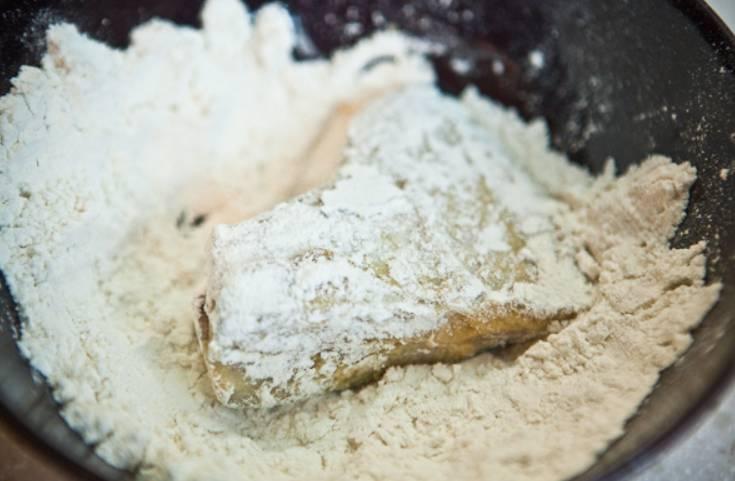Разогреваем масло на сковороде. В миску насыпьте муку. Обваляйте рыбу в муке и выложите на сковороду.