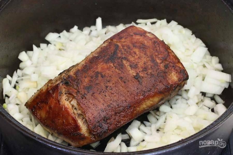 3.Нарежьте кубиками лук и добавьте в казан, обжаривайте несколько минут со сливочным маслом, затем добавьте измельченный чеснок.