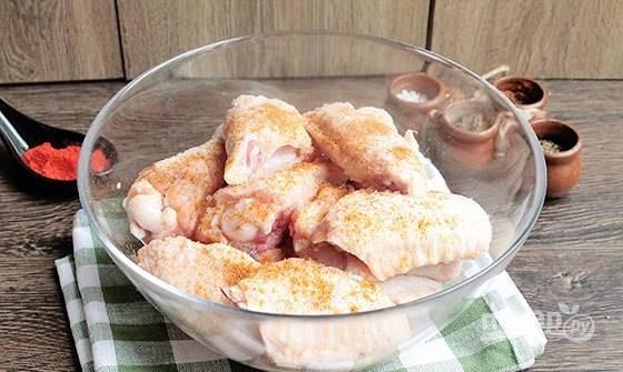 Далее замаринуйте курицу солью и красным перцем. Перемешайте. Оставьте крылья в таком виде на 30 минут.