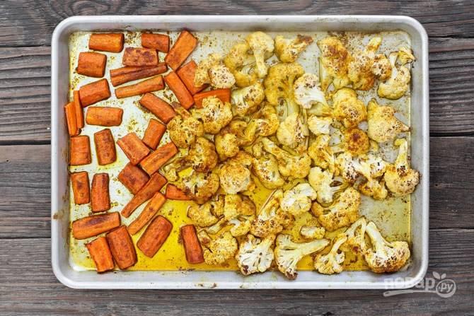 Начинаем с того, что хорошенько промываем и очищаем цветную капусту и морковь. Капусту делим на соцветия, морковь нарезаем полосками. В отдельной емкости смешиваем все специи, а духовку разогреваем до 220-240 градусов. Противень застилаем пергаментом, раскладываем цветную капусту и морковь, посыпая солью и половиной смеси специй. Поливаем оливковым маслом и отправляем в духовку на  минут.