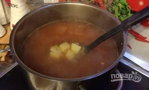 Из готового бульона достаньте мясо кролика. Сам бульон процедите и верните на плиту. Добавьте очищенную и нарезанную картошку и нашинкованную капусту. Накройте кастрюлю крышкой, варите суп пятнадцать минут.