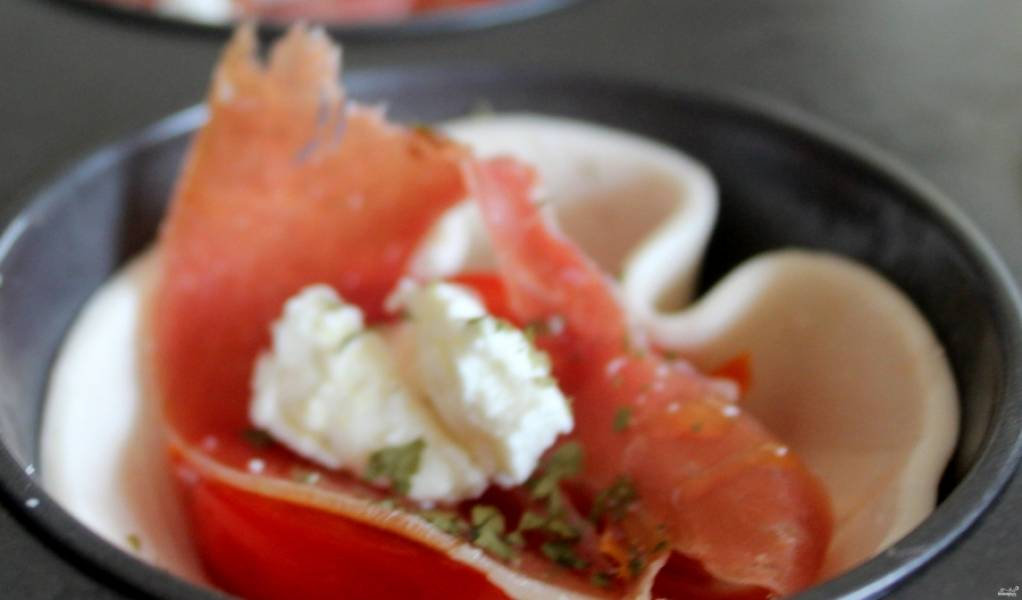 3. На каждый кусочек теста выкладываем половинки помидоров, затем ломтик ветчики, немного сыра и специй. отправим в духовку.