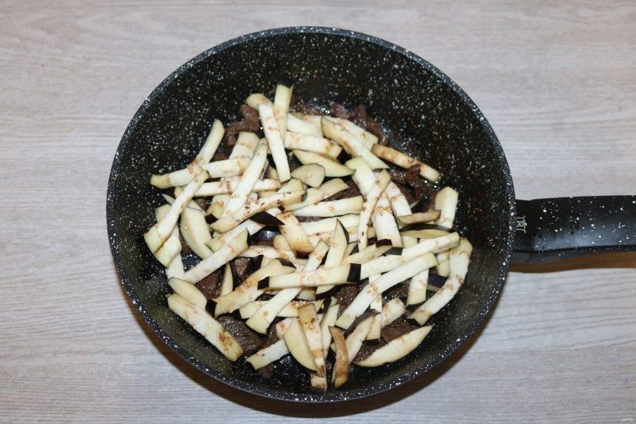 К мясу добавьте баклажаны, обжаривайте вместе на среднем огне.