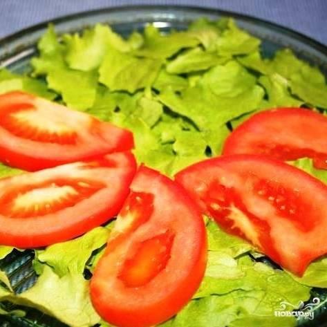 Выкладываем дольки помидора на листья салата.
