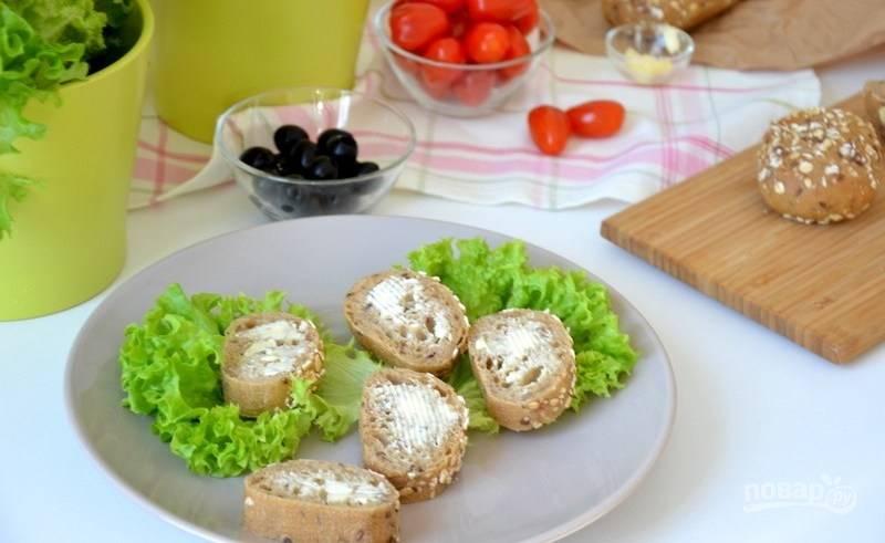 Тарелку украсьте зелеными листьями салата. Бутерброды смажьте маслом или майонезом и выложите на хлеб моцареллу.