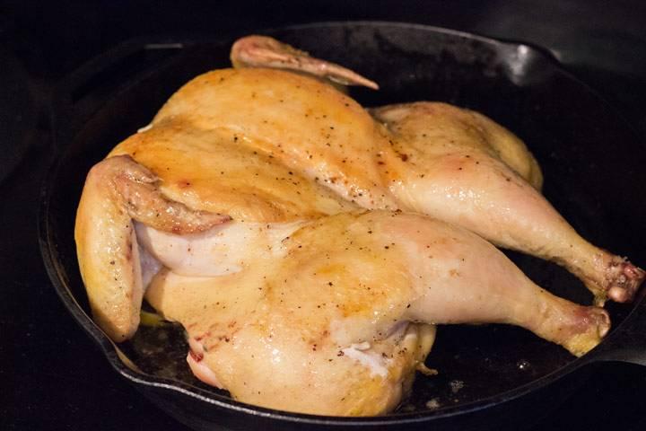 Верните курицу на противень. Снова поместите в духовку, уменьшив температуру до 170 градусов. Запекайте около 40 минут, периодически поливая курицу выделяющимся соком и жиром.