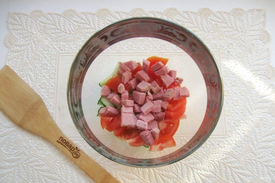Ветчину нарежьте кубиками и добавьте в салатник.