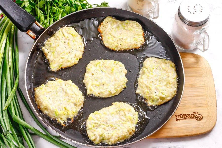 Разогрейте сковороду, влейте на нее растительное масло. Убавьте нагрев до среднего, с помощью столовой ложки выложите в масло порции кабачковой массы. Обжарьте с одной стороны примерно 1-2 минуты.