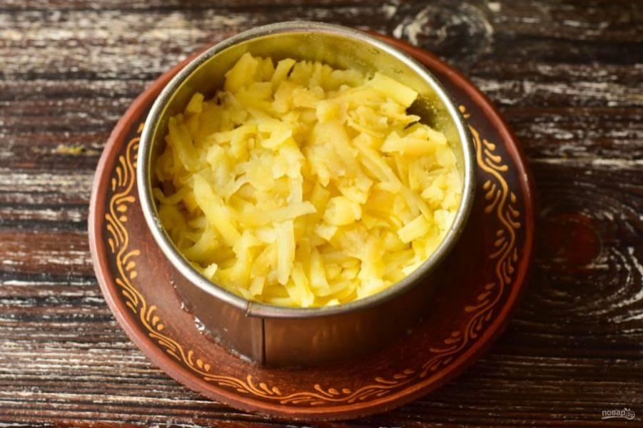 Смажьте их майонезом и выложите тертый вареный картофель. Посолите и поперчите его.