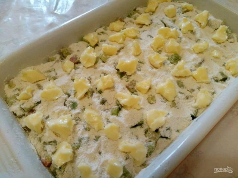 Сливочное масло нарежьте небольшими кусочками и равномерно распределите по всей поверхности пирога. Выпекайте насыпной пирог с ревенем при температуре 180-190 градусов в течение 45-50 минут.