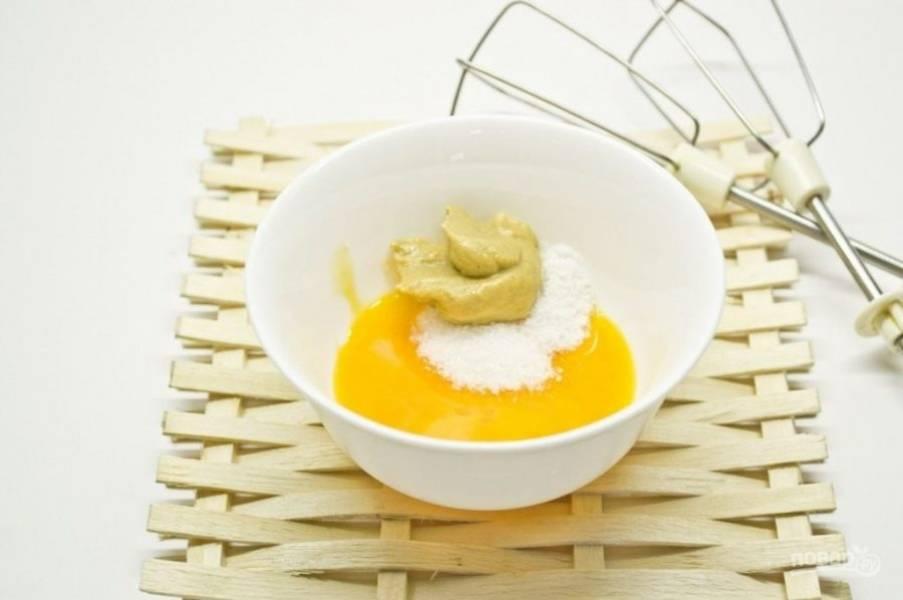 Желтки отделите от белков. Соедините желтки с горчицей, солью и сахаром.