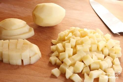 Очищенный картофель нарезаем мелкими кубиками и отправляем вариться в бульон. Немного солим.