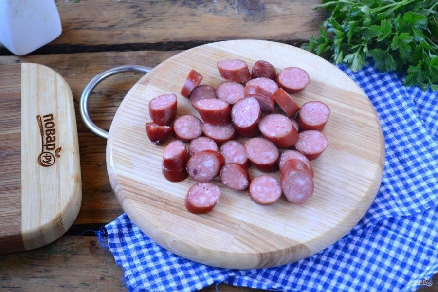 Охотничьи колбаски порежьте небольшими кусочками.