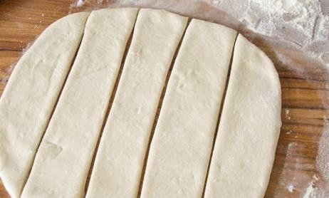 Тесто разделите на 2 части, затем раскатайте их в пласты толщиной 7-8 мм. Каждый пласт порежьте на полоски.