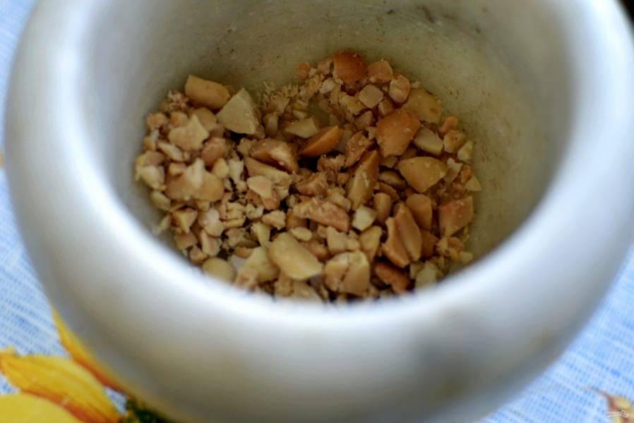 Соленый арахис крупно потолките в ступке или нарежьте ножом. Всыпьте в миску с овощами.