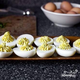 4. В небольшой сковороде разогреть оливковое масло на среднем огне. Добавить анчоусы и измельченный чеснок. Жарить, помешивая, до тех пор, пока анчоусы не начнут растворяться в масле, примерно 1 минуту. Добавить лимонную цедру, панировочные сухари и обжарить их до золотистого цвета, около 2-3 минут. Перемешать с тертым сыром Пармезан и отложить смесь в сторону. Заполнить белки начинкой из желтков. Вы можете использовать для этого кондитерский мешок с наконечником в виде звезды – это сделает блюдо красивым.