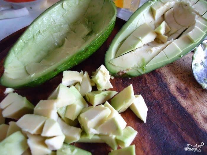 Авокадо порежьте пополам, достаньте косточку. С помощью ножа и ложки аккуратно достаньте мякоть и порежьте ее на кубики.