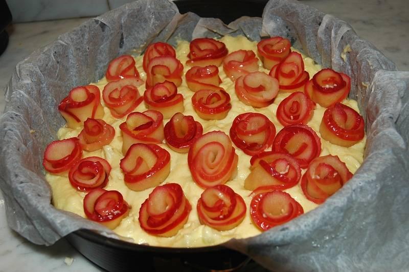 6. Форму для запекания смазать маслом или застелить пергаментом. Выложить тесто и разровнять. Сверху высадить розочки, немного утопив их в тесте. Отправить форму в заранее разогретую духовку на 40-45 минут.